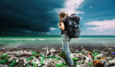 A woman at a beach covered in waste