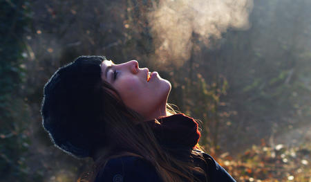 A woman exhaling in a cold weather