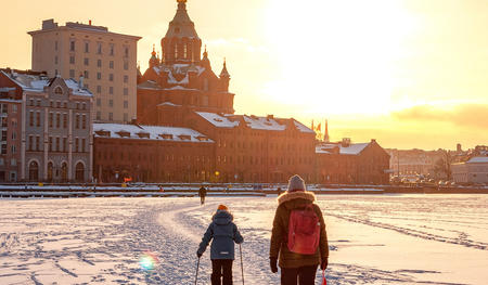 Helsinki in Winter, people skiing on the frozen sea towards Katajanokka