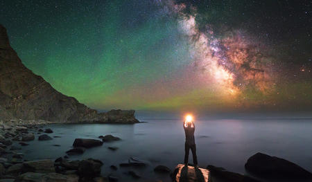 A person looking at the sky filled with stars holding a light in their hands