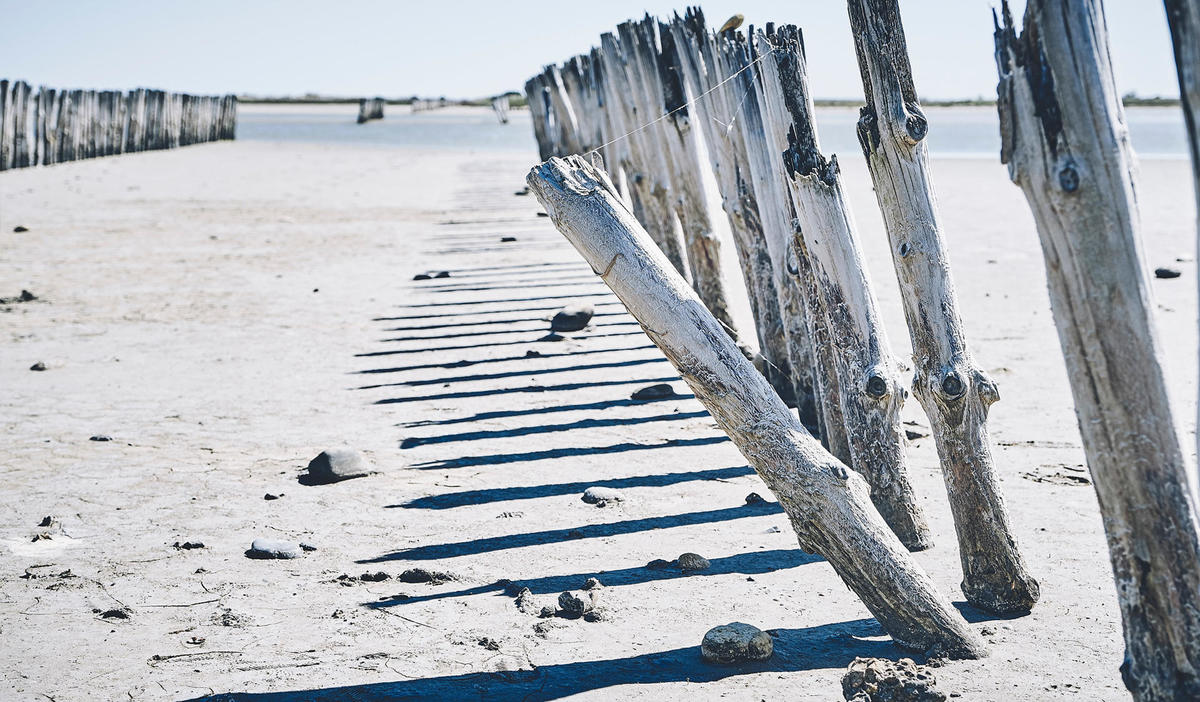A white wooden fence on an empty beach