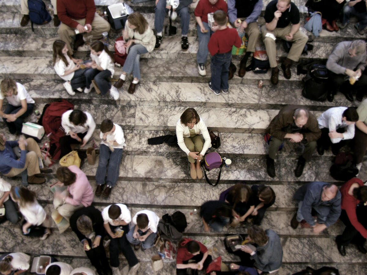 women sitting alone in crowded steps