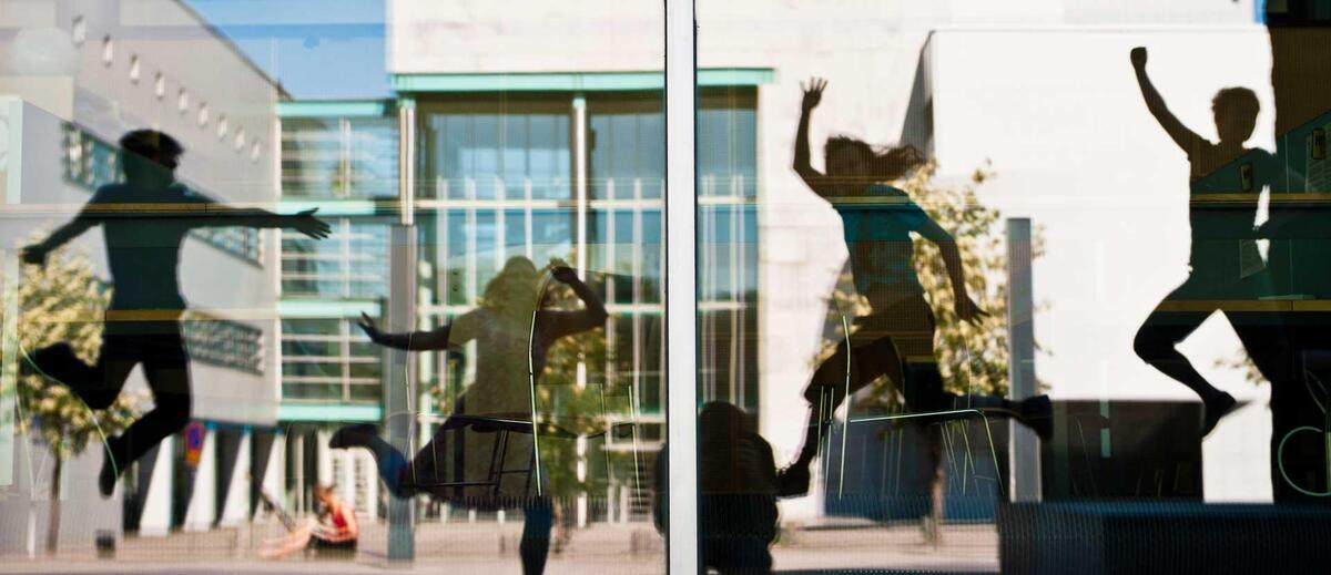 Reflections in the window of jumping University of Helsinki students at the Kumpula Campus.