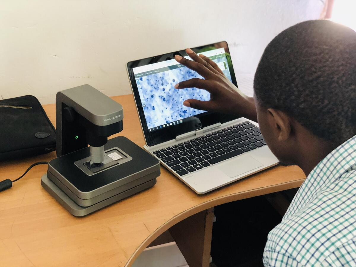 Laboratory manager Martin Muinde scanning the pap smear samples with portable scanner and looking at the digitized sample from a laptop.