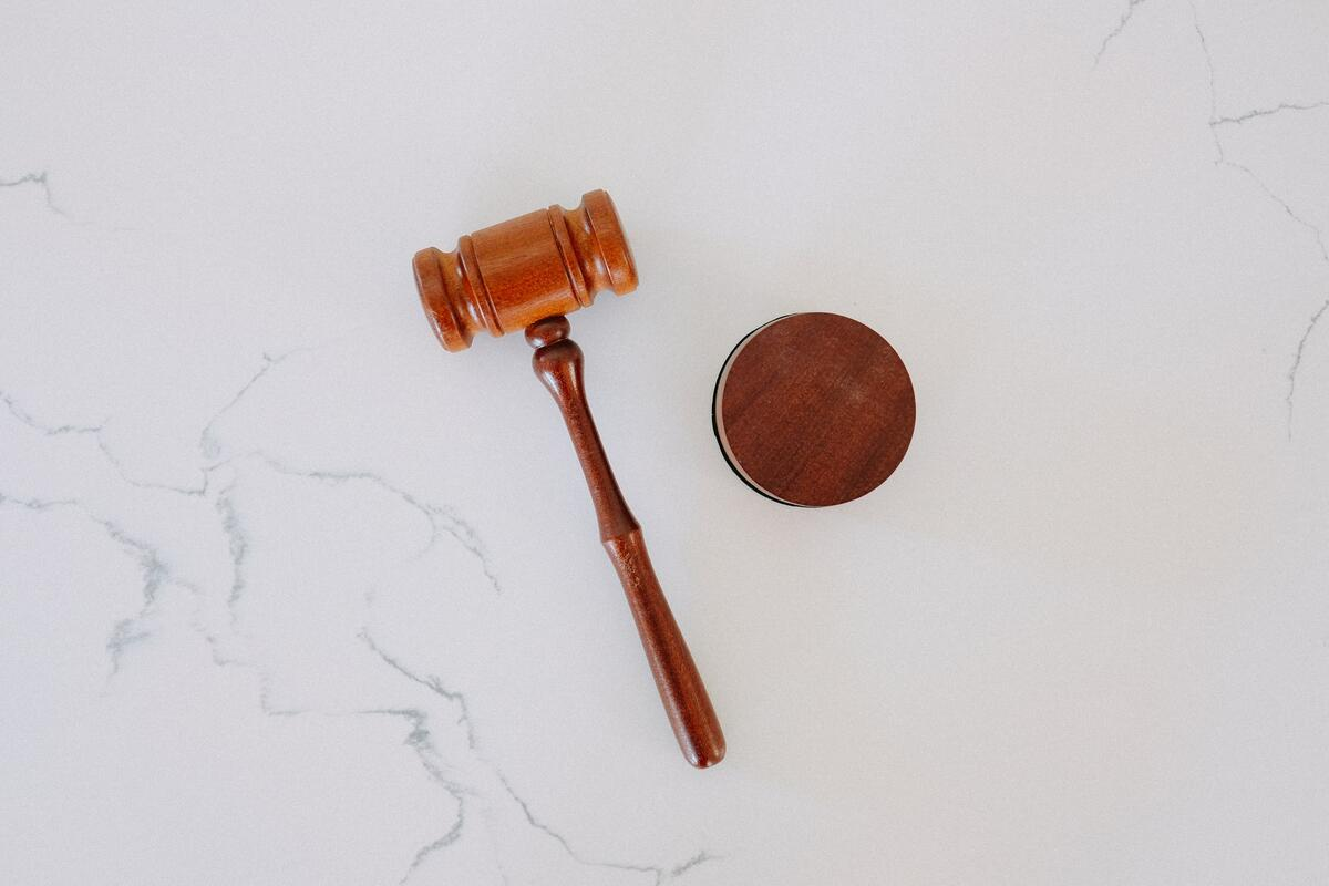 A judge's hammer on a white marble table.