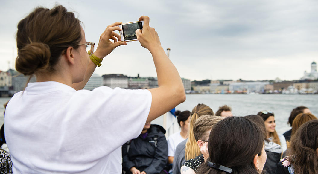 Helsinki Summer school: picture for contact information, student with a phone