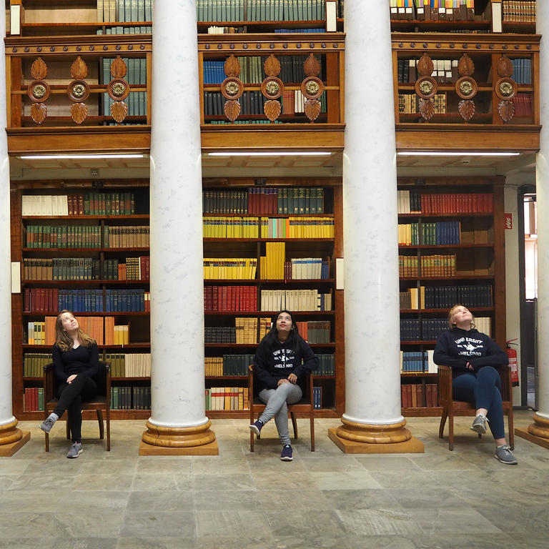 Three student ambassadors sitting in a library in front of big bookshelf
