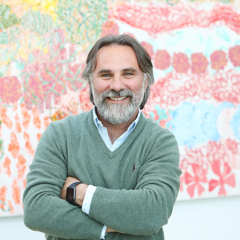 Vincenzo Cerullo standing in front of a light coloured art work.