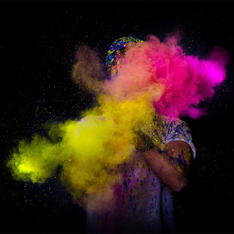 Yellow and pink smoke. Behind the smoke one person. Black background.