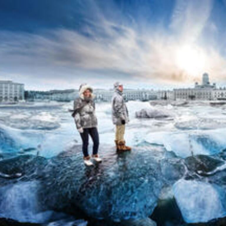 A wintery image with two people standing on ice floes with the city of Helsinki in the background.