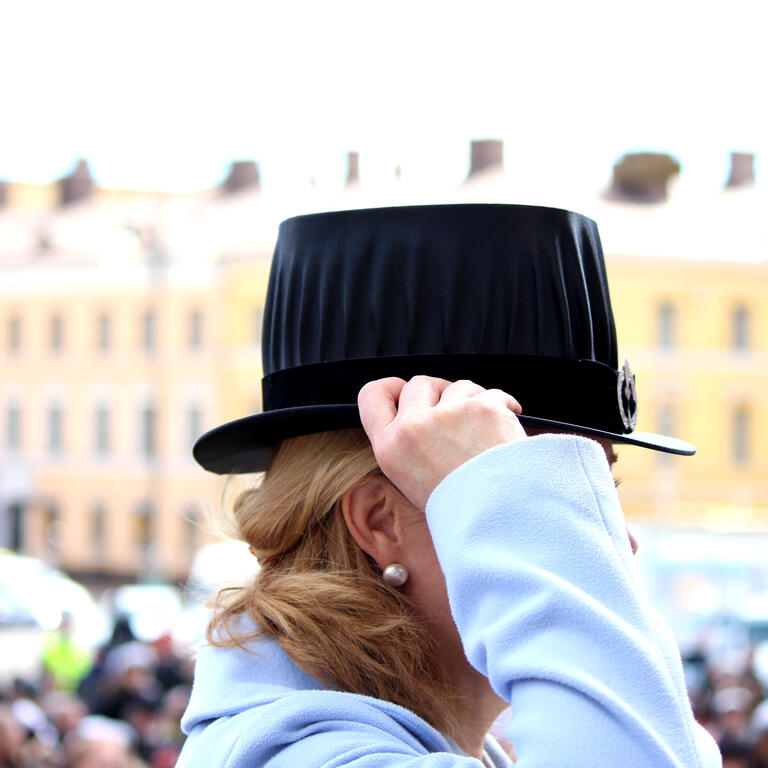 A woman holding a doctoral hat.
