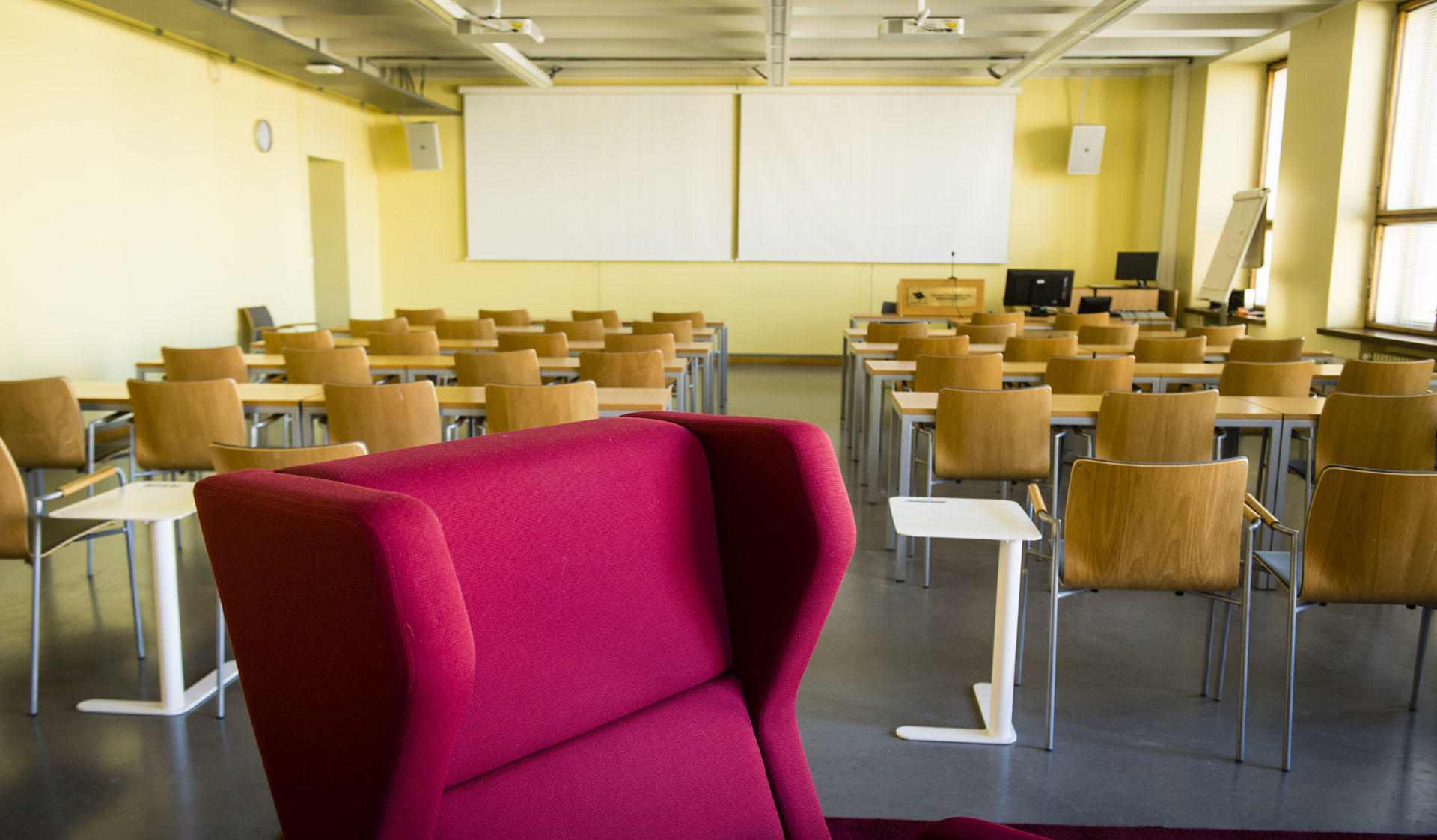Empty seminar space at the Collegium's Common room with tables, chairs and an arm chair.