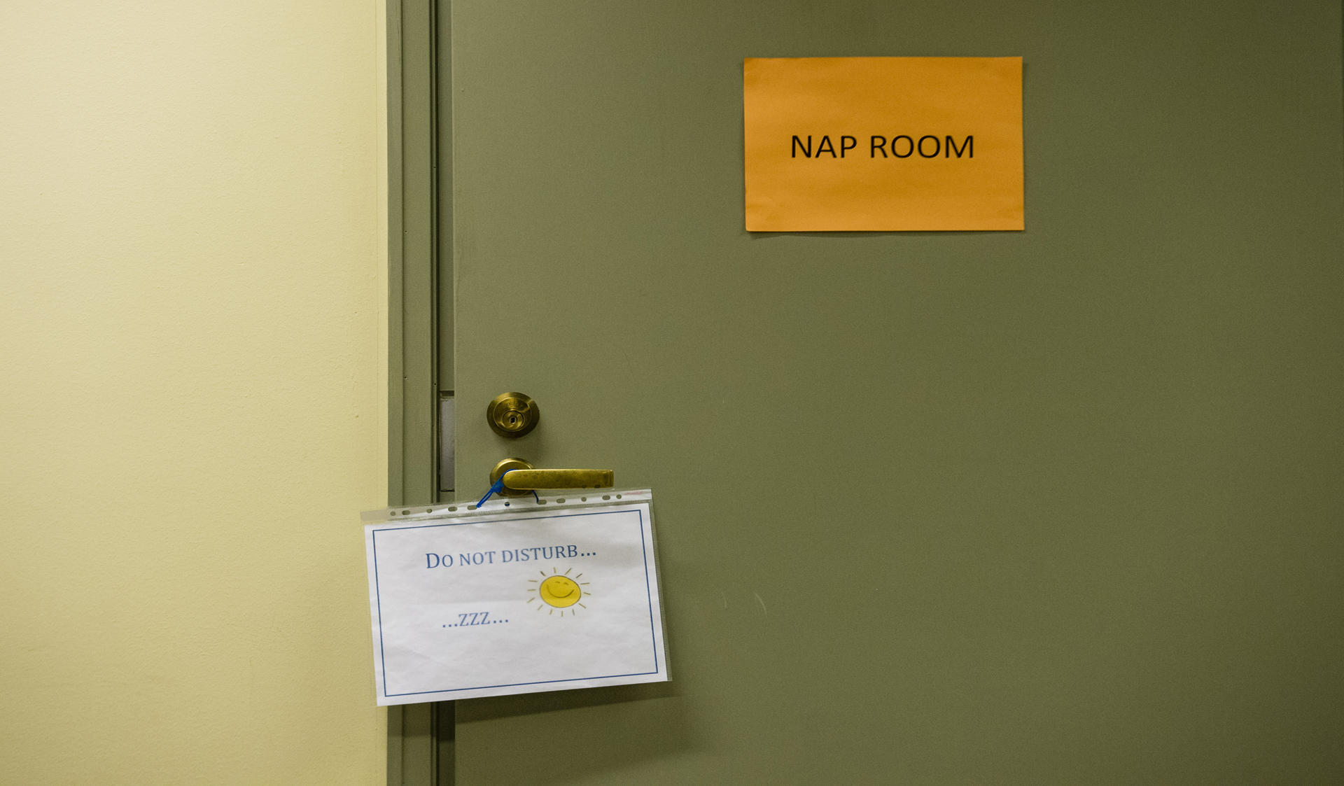 """A door that has a paper with the text """"nap room"""" on it. A sign with the text """"do not disturb"""" is hanging from the door handle."""
