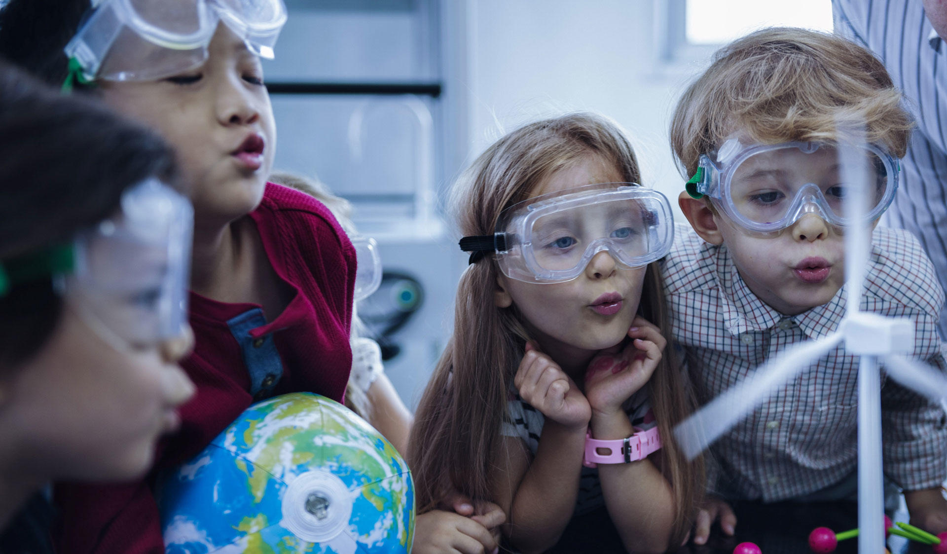 Children with protective masks in a classroom learning about science and the world. Image of the Master's Programme in Changing Education at the University of Helsinki.