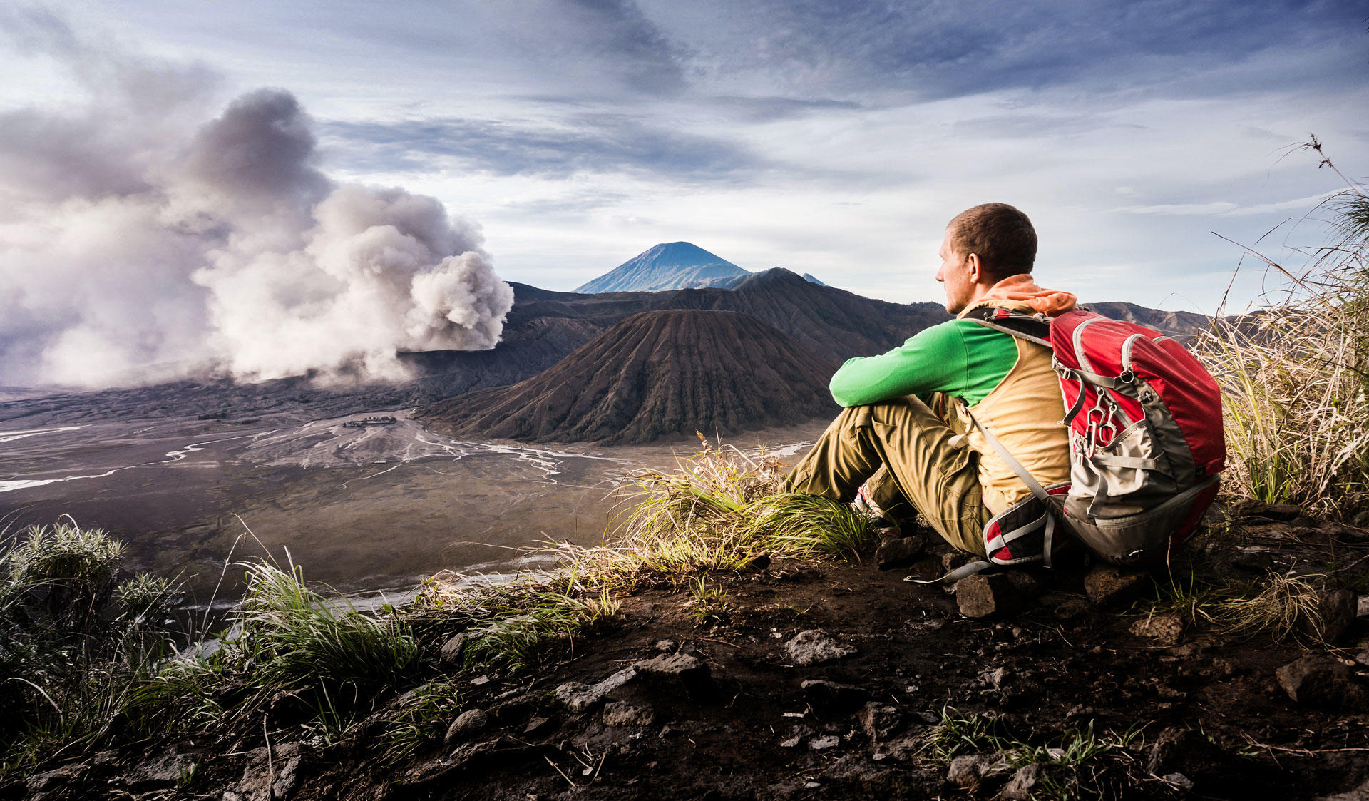 A boy sitting on a hill watching an erupting volcano. Image of the Master's Programme in Geology and Geophysics at the University of Helsinki.