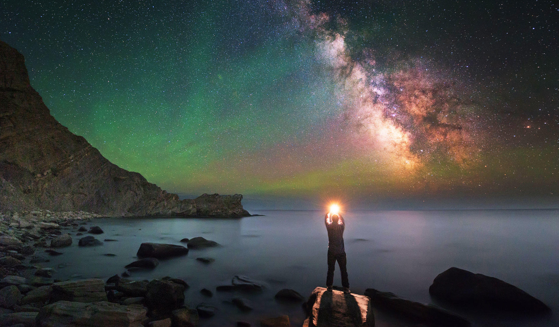 Man holding a light and standing on a rock by the sea and colourful sky. Image of the Master's Programme in  Particle Physics and Astrophysical Sciences at the University of Helsinki.