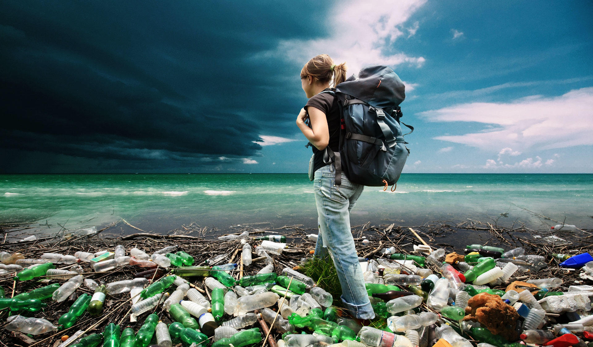 Girl with a backpack standing on a beach full of garbage looking at the sea.