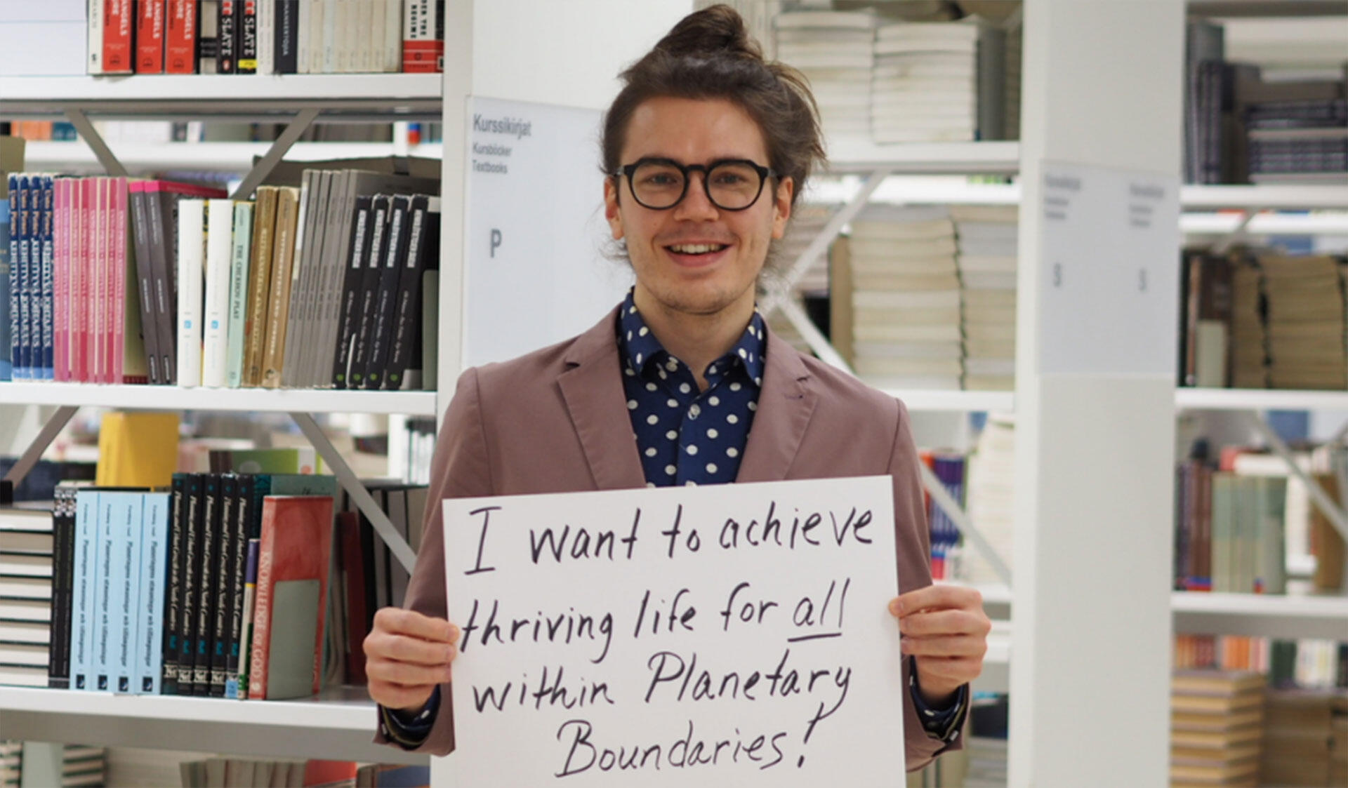 """Jack H. Raisanen, Master's student in Atmospheric Sciences, holding a sign saying """"I want to achieve thriving life for all within Planetary Boundaries""""."""