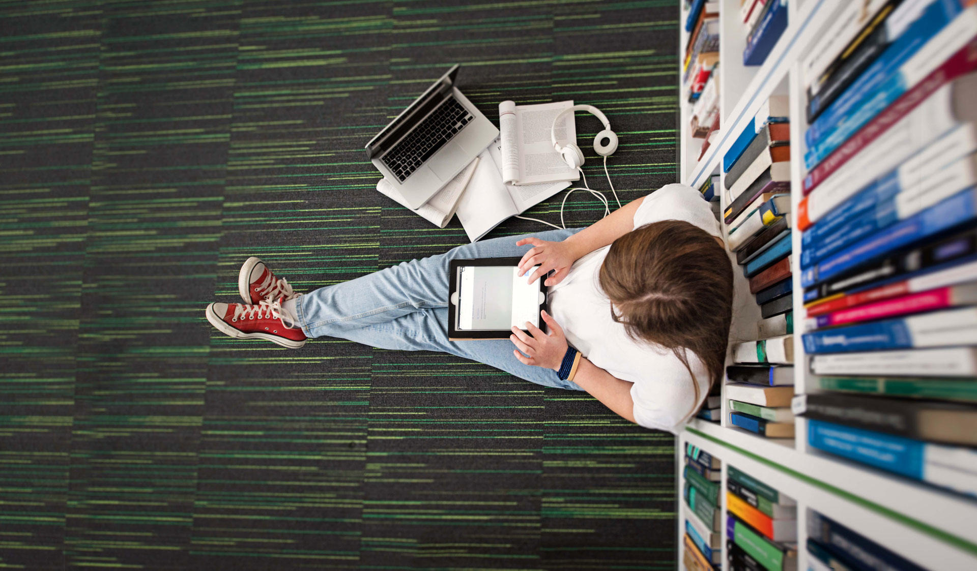 Image of a person sitting on the floor and studying in the library.