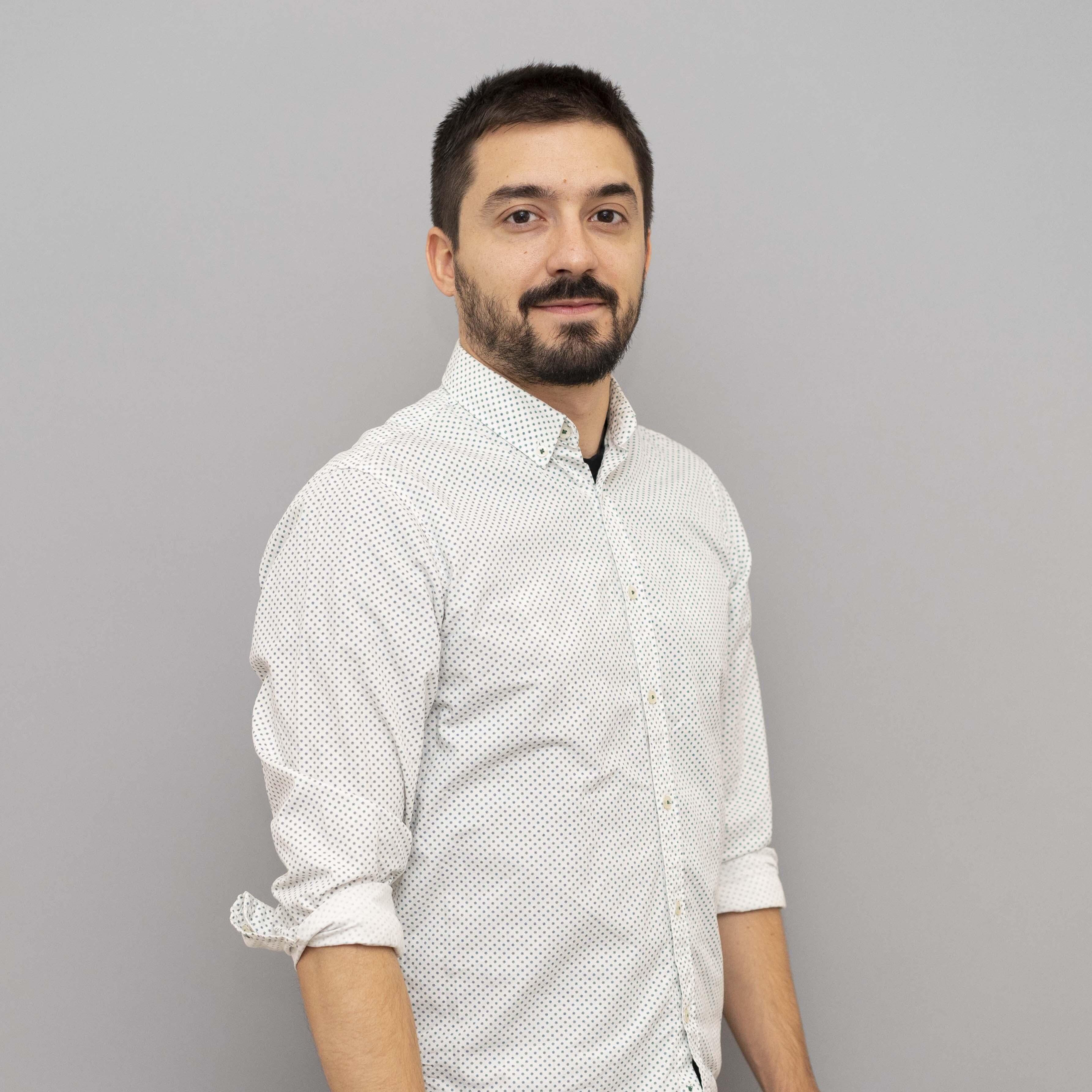 Man in white shirt standing in front of a light gray background