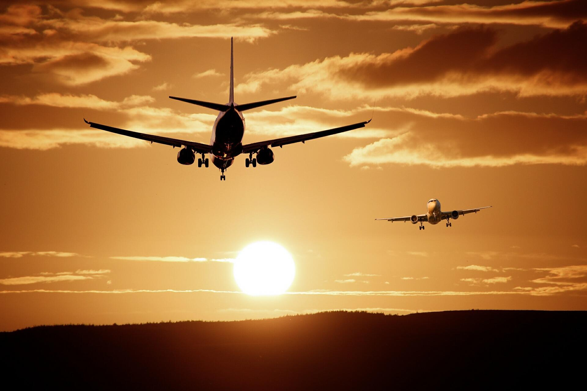 Two airplanes in the sunset.